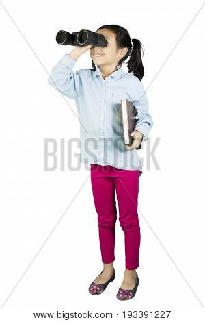 Schoolgirl looking something with binoculars while holding a textbook isolated on white background