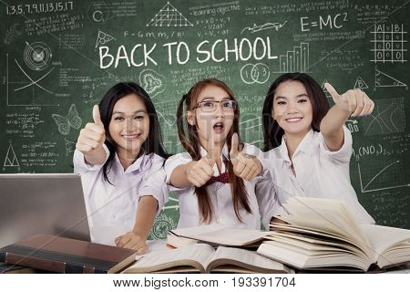 Concept of Back to School. Group of three beautiful high school student showing thumbs up with book on the table and a text of Back to School on chalkboard shot in classroom