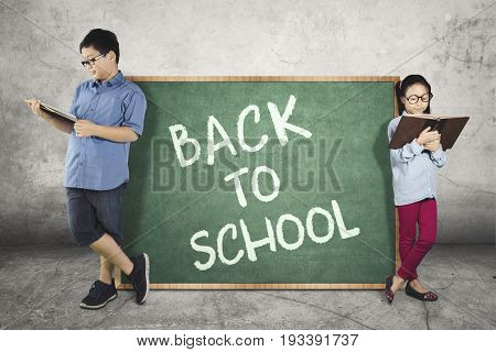Image of cute two children studying with a book while leaning on a text of back to school on the chalkboard