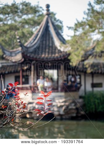 Suzhou, China - Nov 5, 2016: Master of Nets Garden (Wang Shi Yuan) - Focus on foreground red leaves, with background pavilion and people defocused.