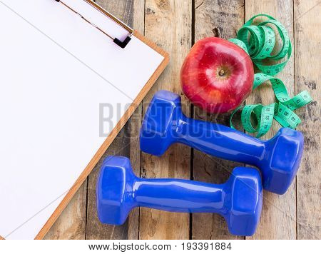 Medical form with blue dumbbell white towel measuring tape and red apple on wooden table. Fitness concept