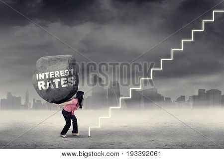 Female worker carrying a boulder with text of interest rates and walking toward a stair. Concept of big interest rates