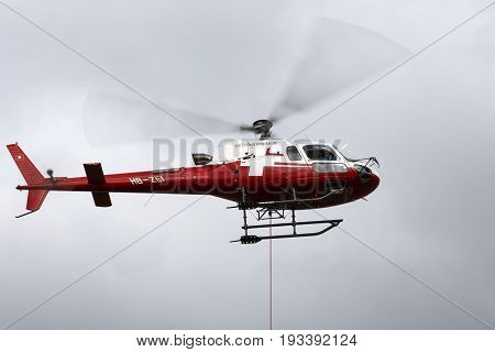 Bern Switzerland - April 19 2017: Eurocopter AS350 B3 in colors of a Swiss Helicopter airlines. The hanging rope is a sign that the machine is in a cargo transport operation.