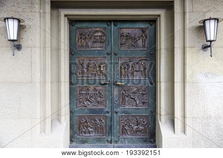 Bern Switzerland - April 17 2017: Massive church doors are decorated with eight brass rectangular bas-reliefs depicting religious scenes.