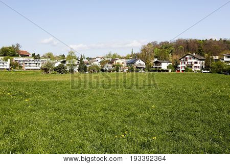 Bern Switzerland - April 14 2017: Spring green meadow completed with a number of residential homes is an example of the tranquility of the landscape that you can see from the Murifeld of Bern