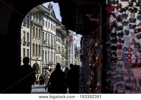 Bern Switzerland - April 20 2017: Through the shaded gate several people pass. Somewhat in the distance the city's historic buildings are illuminated by sunlight