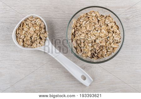 Rye Flakes In Transparent Bowl And Plastic Spoon