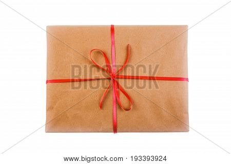 Gift in wrapping paper tied with red ribbon isolated on white background top view close-up