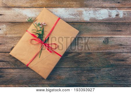 gift wrapping paper tied with a red ribbon and a Daisy flower on wooden retro grunge background with space for text top view closeup