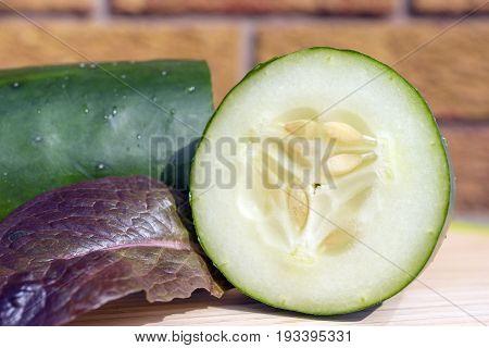 Healthy Raw Crisp Cucumber Sliced In Half On Wooden Cutting Board Beside Leaf Of Purple Lettuce