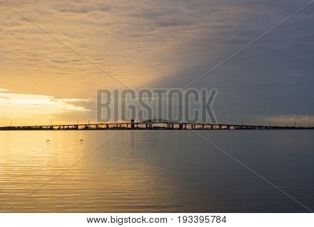Peaceful Blue And Golden Colorful Sunrise Over Skyway Bridge And Calm Lake Waters, Dramatic Sky And