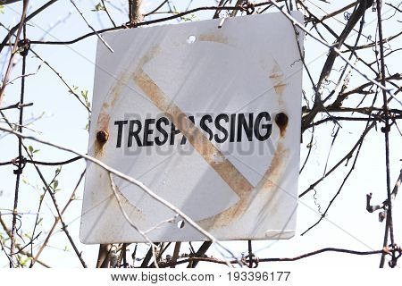 Closeup Of Old And Weathered No Trespassing Sign Posted To Wire Fence, Safety Concept