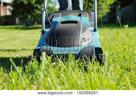 Lawn mower close-up. A machine is mowing a grass.