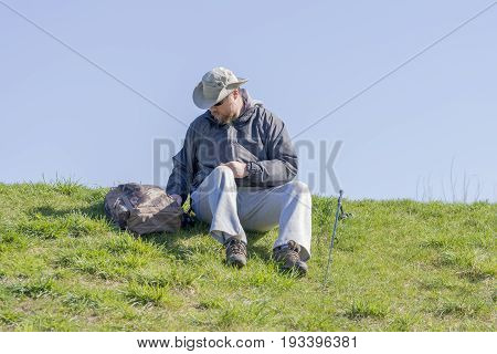Man Getting Ready To Fish From A Grassy Riverbank, Sitting And Looking Through His Gear
