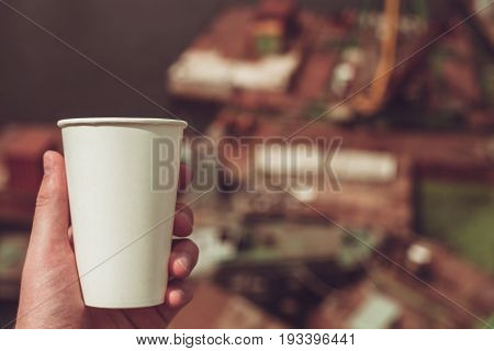 Paper cup on a background of urban landscapes.