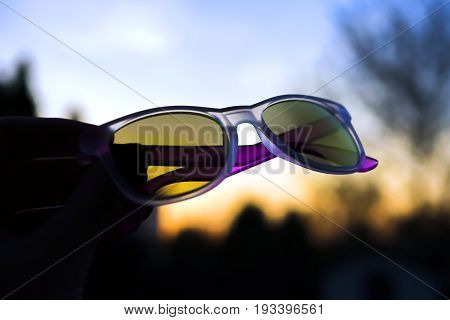 A Pair Of Colored Summer Sunglasses Held Up In Front Of An Evening Sunset