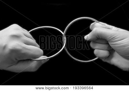 Two Hands Pulling Rings Apart That Are Joined Together