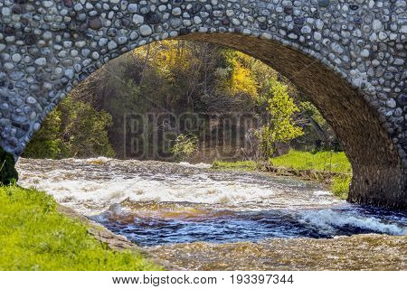 Archway Of Stone Bridge Over Swift Flowing River Leading To Drop Off The Edge Of A Waterfall