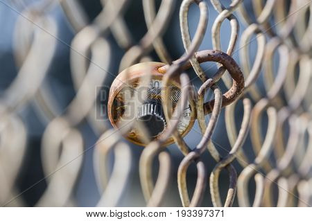 Broken And Rusty School Combination Lock On Chain Link Fence