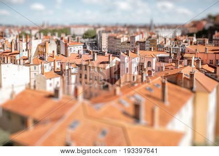 Cityscape view on the old town with red tiled roofs in Lyon, France. Tilt-shift image technic