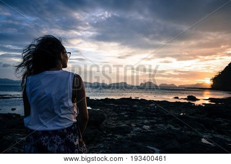 EL NIDO, PALAWAN, PHILIPPINES - MARCH 29, 2017: Woman find peace with the beautiful sunset at Las Cabanas Beach.