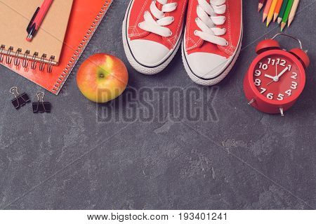 Back to school background with school supplies over blackboard. Top view. Flat lay