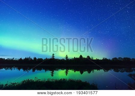 Vibrant Green And Pink Northern Lights And Bright Stars Reflecting In Calm Water