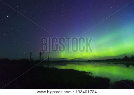 Night Landscape With Stars In Deep Blue Sky To Left And Nothern Lights Glowing Over Lake On Right