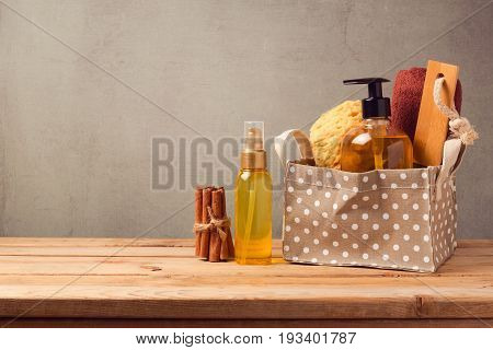 Body care and personal hygiene products on wooden table over gray background