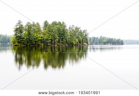 Island In Northern Climate With Tall Pine Trees Hiding A Vacation House