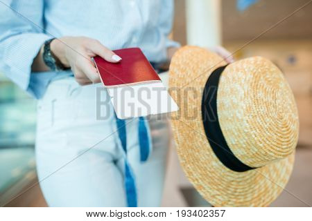 Closeup of woman holding passports and boarding pass at airport