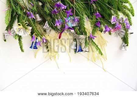 christmass tree brunches decorated with a bells and bell flowers in a row above copy space for your text at the bottom. new year and christmas conceptual greeting card.