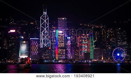 Hong Kong Iconic Red Vintage Sail Boat Sailing At Night Skyline Background