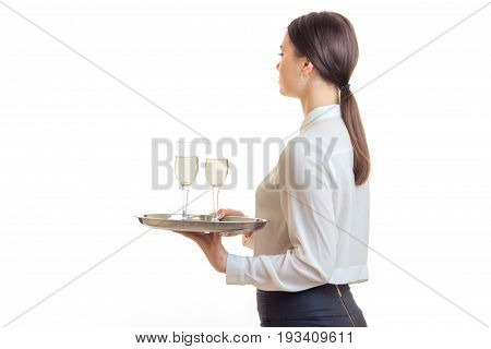 Young brunette waitress in uniform with trey in hands isolated on white background