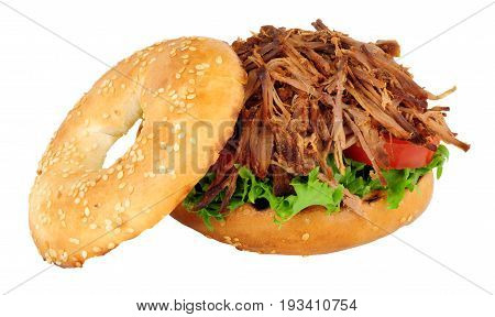 Slow cooked shredded beef and salad filled bagel sandwich isolated on a white background