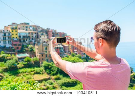 Tourist looking at scenic view of Corniglia, Cinque Terre, Liguria, Italy