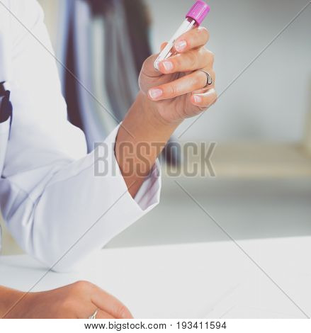 Woman researcher is surrounded by medical vials and flasks