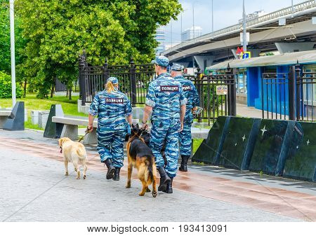 Russia, Moscow - July 12/2016: Policemen And Dogs Patrol The Park Near The Exhibition Of Achievement