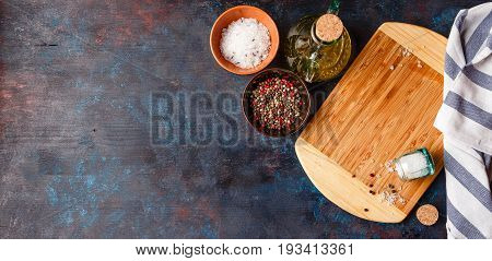 Cutting Board olive oil salt and pepper on dark table