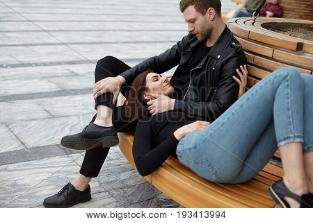 Cute couple cuddling on bench sharing happy moments of love and tenderness. Beautiful girl wearing jeans lying on lap of her attractive bearded boyfriend in leather jacket who is touching her face