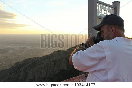 A Photographer Shoots Images on the Sandia Peak Aerial Tramway Observation Deck at Sunset