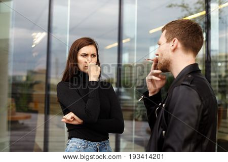 Passive smoking concept. Confident handsome young male taking drag on cigarette ignoring requests of his girlfriend to stop smoking disgusted female pinching her nose annoyed with tobacco smell
