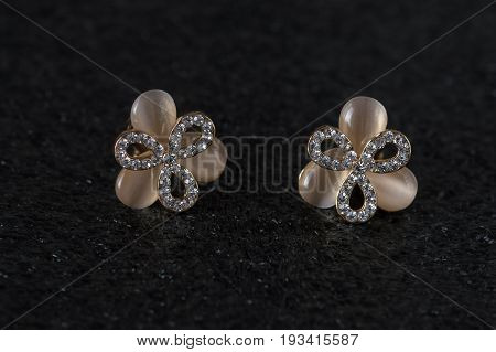 Beautiful earrings with stones. Jewelery clips and earrings. Delicate earrings on a black background