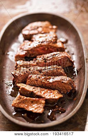 Sliced angus steak on iron cast with juices
