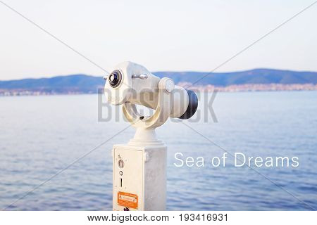 A telescope on the sea-summer, the sun, the sea, the beach. The inscription dream of the sea