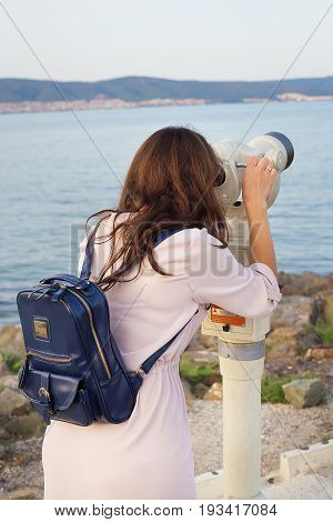 The girl looks through the telescope at the sea