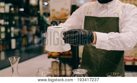 Tasting Large Leaf Tea On A White Background. A Man In Gloves Brews Tea In A Glass Container Close-u