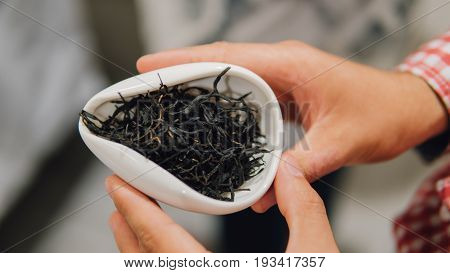 Black Large-leaf Tea In A White Porcelain Bowl Of Close-up. Chilled Chinese Tea In A White Bowl Shal