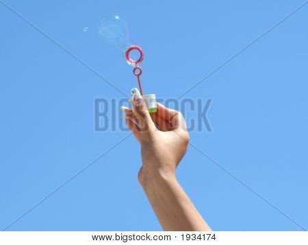 Female Hand And Soap Bubbles On A Background Of The Blue Sky