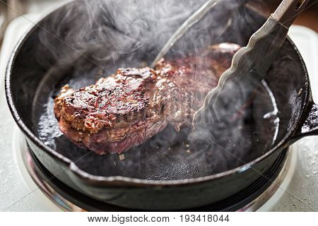 Angus steak fried on vegetable oil on iron cast